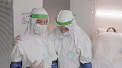 Doctor Supporting Colleague Wearing Hazmat Suit