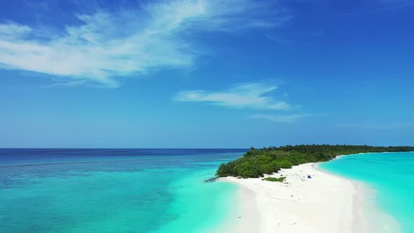 Beautiful fly over travel shot of a sandy white paradise beach and aqua blue water background in hig
