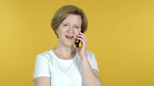 Old Woman Talking on Smartphone Isolated on Yellow Background