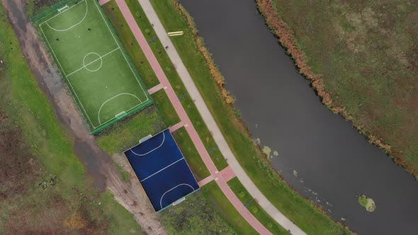 Football playing fields from bird's eye view. Recreation and sports zone on city quay along river