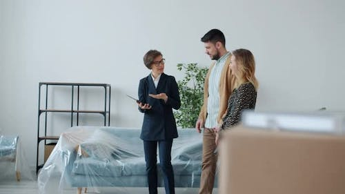 Real Estate Broker Using Tablet and Showing New House To Buyers Man and Woman Talking Gesturing