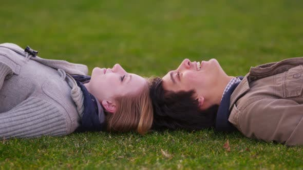 Thumbnail for Young couple laying in grass pointing at clouds