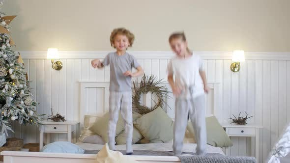 Thumbnail for Little Kids Jumping on Bed in Room Decorated with Christmas Tree