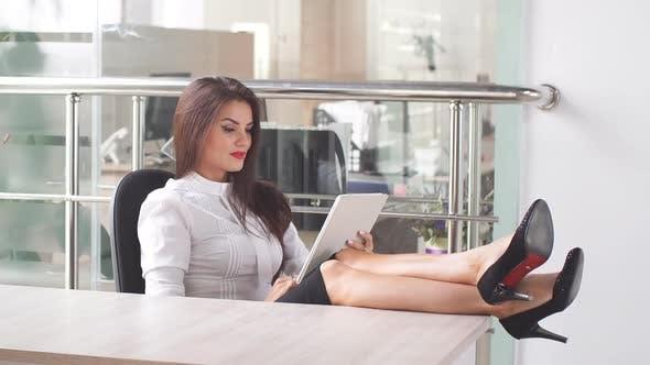 Thumbnail for Female Office Worker Swung Her Legs Over Her Desk