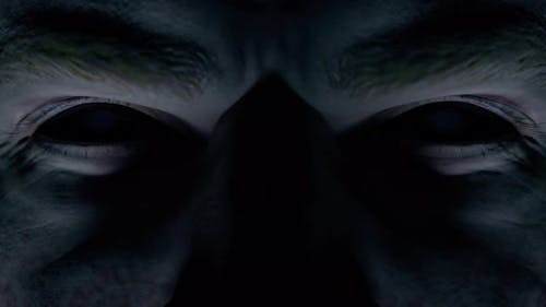 Scary Menacing Gaze of a Man with Empty Black Eyes Close-up