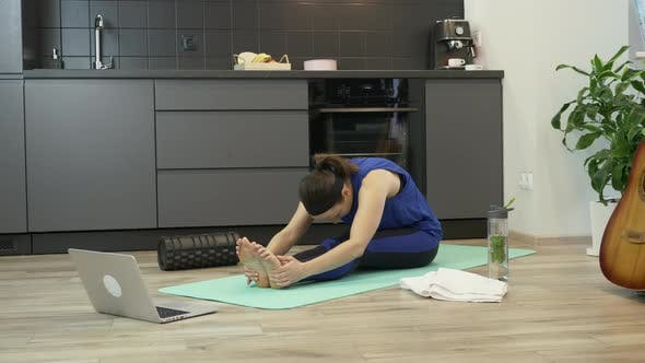 Thumbnail for Young girl doing online stretching and yoga exercises using fitness app on notebook computer at home