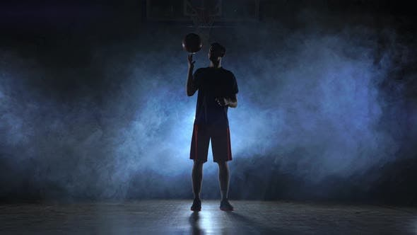 Thumbnail for Close Footage of Basketball Player Spinning Ball on His Finger, Dark Misty Room with Floodlight