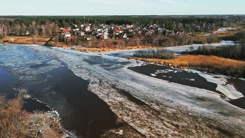 Small Town at Bank of River Gauja with Melting Ice and Snow in Spring Rising Shot