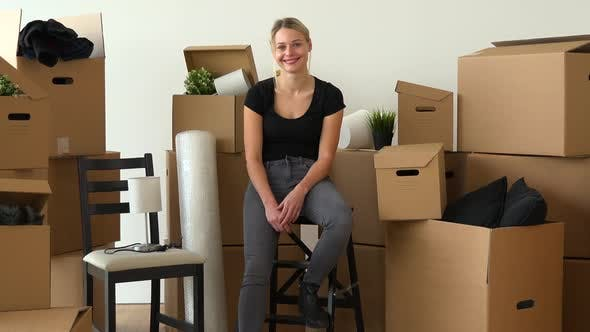 Thumbnail for A Happy Moving Woman Sits on a Chair and Smiles at the Camera in an Empty Apartment