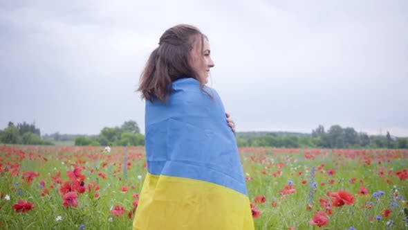 Thumbnail for Pretty Girl Standing in a Poppy Field Covered with Flag of Ukraine