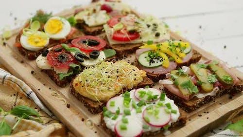 Leckere, hausgemachte kleine Sandwiches mit verschiedenen Zutaten serviert auf Holz-Schneidebrett