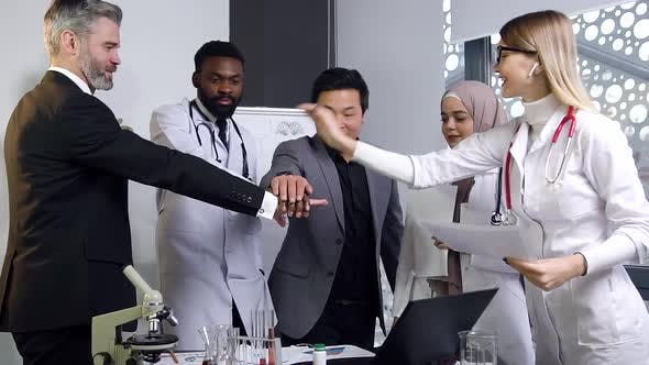 Mixed Race Group of Doctors Puts Palm Together on Centre and Rejoices