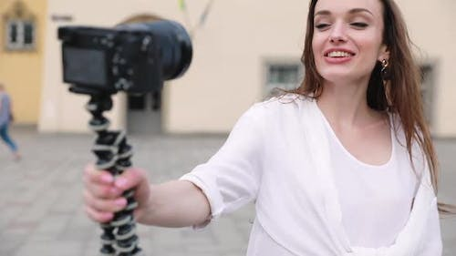 Woman recording video for vlog on camera outdoors.