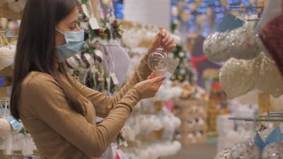 Professional Shopper in Face Mask Holds Transparent Bauble