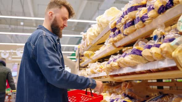 Man Buying Bread in the Supermarket After Checking Sellby Date