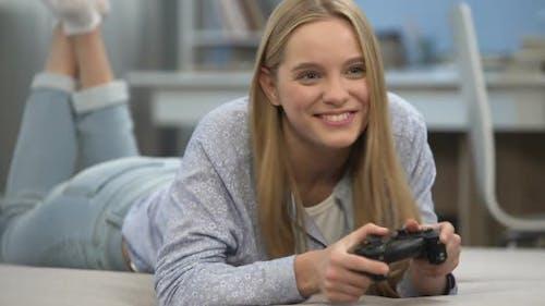 Teenage Girl Gamer Playing Shooter With Joystick