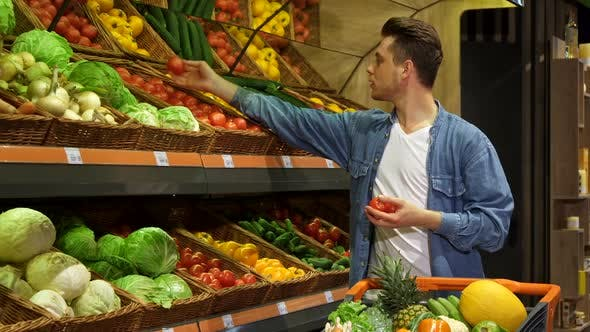 Cover Image for Man Takes Tomatos and Cucumber From the Rack at the Supermarket