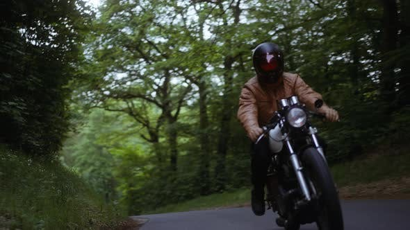 Person Driving With a Motorcycle on a Narrow Road in the Forest
