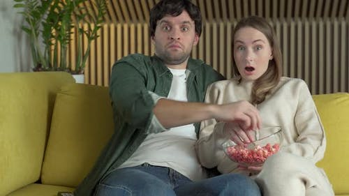 Young Couple Is Sitting on a Yellow Sofa Eating Popcorn and Watching a Movie with a Shocked