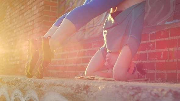Thumbnail for A young woman doing a headstand on the streets on an urban environment.