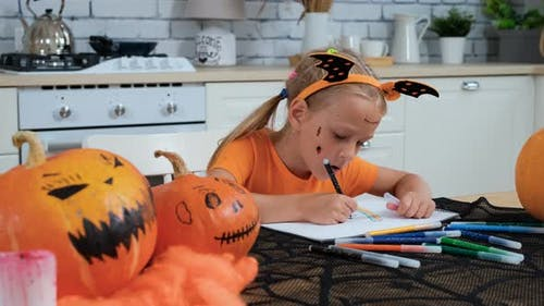 Little Girl Drawing with Felt-Pens in Halloween