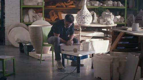 Male Artisan Creating Earthenware on Wheel