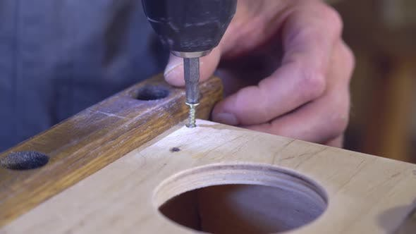 Thumbnail for Man Boring Holes Using Steel Drill Indoors