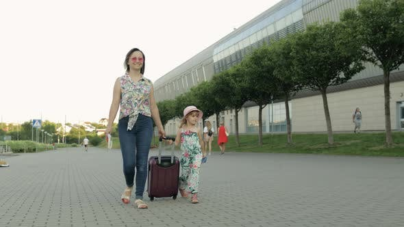 Thumbnail for Mother and Daughter Walking Outdoors To Airport. Woman Carrying Suitcase Bag. Child and Mom Vacation