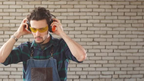 Portrait of a Young Man in a Carpenter's Workshop in Protective Glasses Looking at Camera