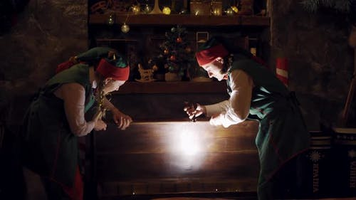 Fairy elves in dark room at Christmas. Excited elves open magic chest