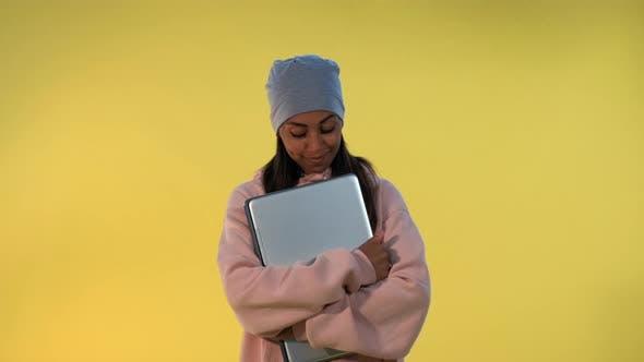 Portrait de fille africaine dans la casquette étreindre son ordinateur portable