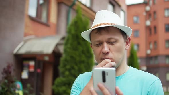 Man in a hat stands on the street of the city, thoughtfully examines the information in his phone