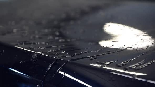 Close Up on Water Drops on Reflective Painted Surface of a Car