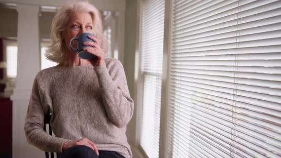 Thumbnail for Elder woman drinking coffee sitting by window looking outside smiling