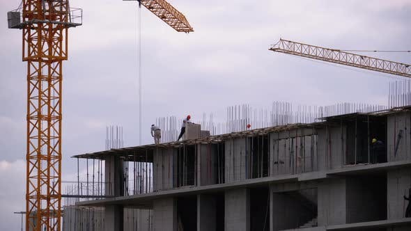 Builders on the Edge of a Skyscraper Under Construction, Workers at a Construction Site