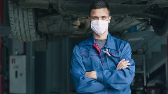 Thumbnail for Portrait of Professional Auto Mechanic Wearing Protective Medical Mask, Posing at Car Repair Station