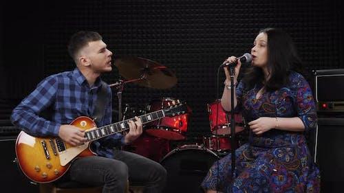 Mann spielt Gitarre und Frau singt Lied