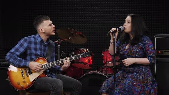 Man playing guitar and woman singing song