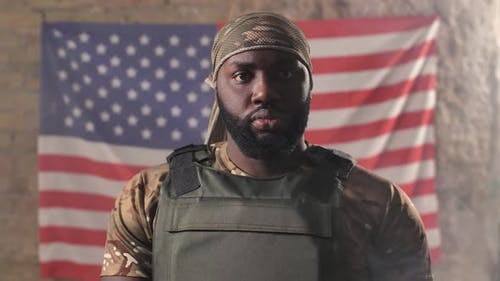 Black Army Man Posing on Background of US Flag