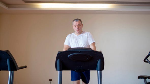 Thumbnail for Middle-Aged Man Working Out on A Treadmill