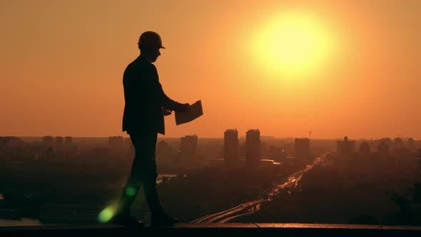 Businessman in a Hard Hat Holding Plan Cityscape at Sunrise