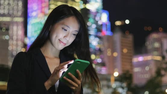 Business woman cellphone at night