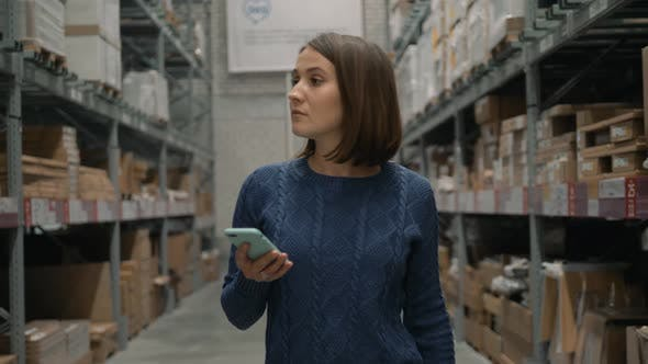 Woman with a Phone Looking for a Product in a Warehouse Store