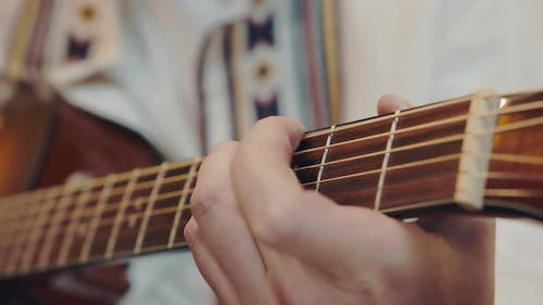 Male Hand Rearranges Chords on Acoustic Guitar Close Up