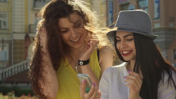 Thumbnail for Two Girls Discuss Something on Smartphone