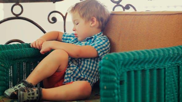 Boy Sitting in  Armchair
