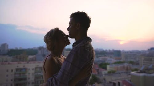 Beautiful Couple Basking in Embraces, Admiring Sunset from Roof of High Building