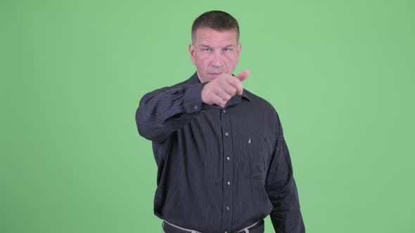Angry Macho Mature Businessman with Threat Gesture