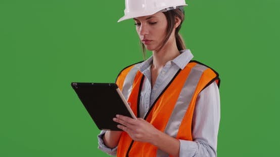 Thumbnail for Woman in orange vest with digital tablet computer and hard hat on greenscreen