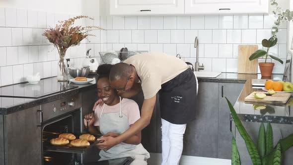 Junge glückliche Familie zu sehen, backen sie im Ofen gekocht.